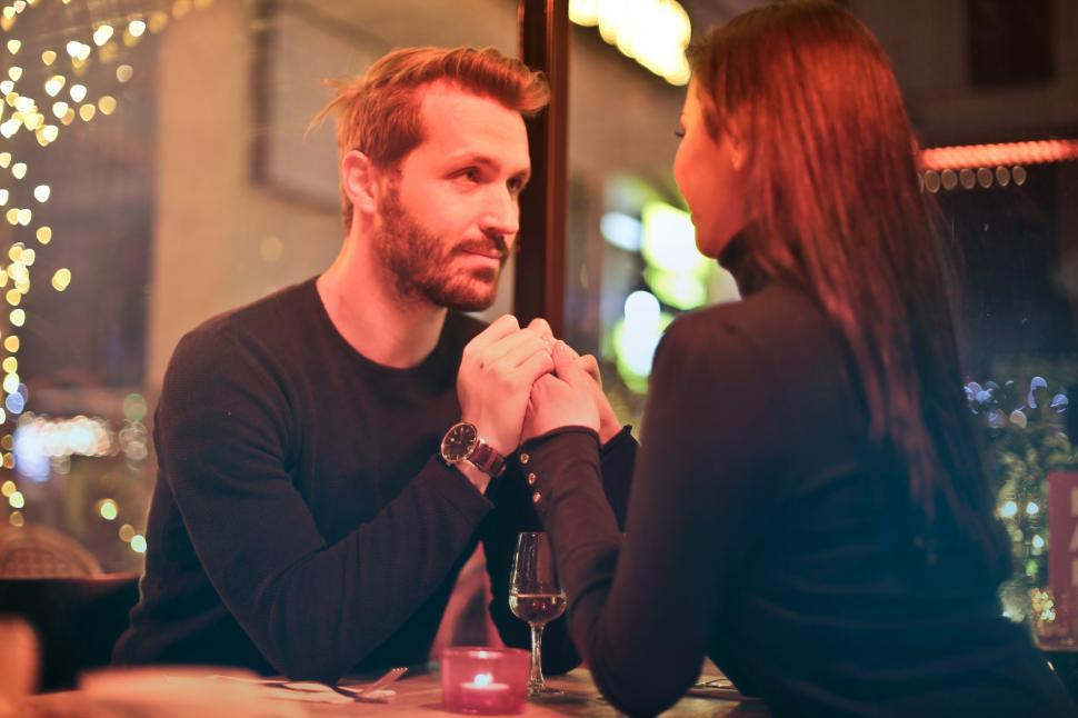 Download Free Stock HD Photo of Romantic couple holding hands together during a romantic dinner Online