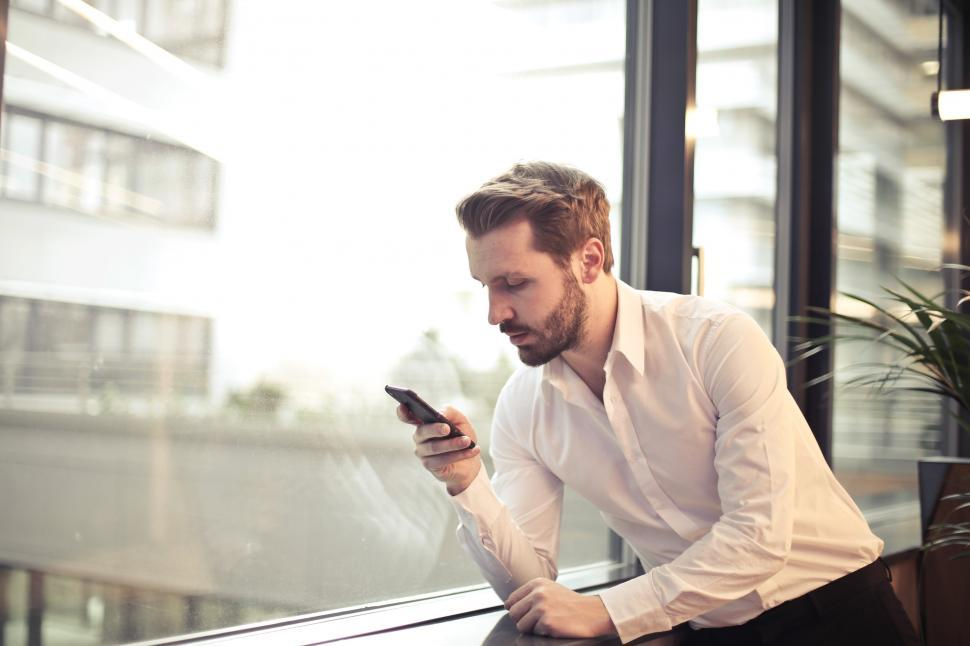 Download Free Stock Photo of Young Adult Man in White Shirt Holding Phone Near Window