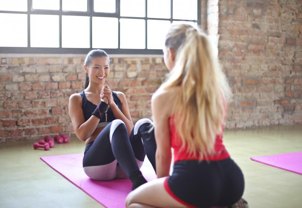 Download Free Stock Photo of Two Woman In Red Top And Black Bra Doing Exercises On Purple Yog