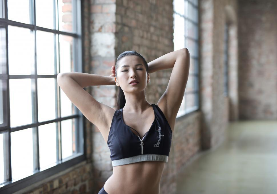 Download Free Stock HD Photo of Young Woman Wearing Black Sports Bra Posing In Gym Online
