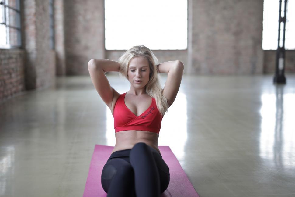 Download Free Stock Photo of Woman Wearing Red Sports Bra lying on yoga mat and doing crunche
