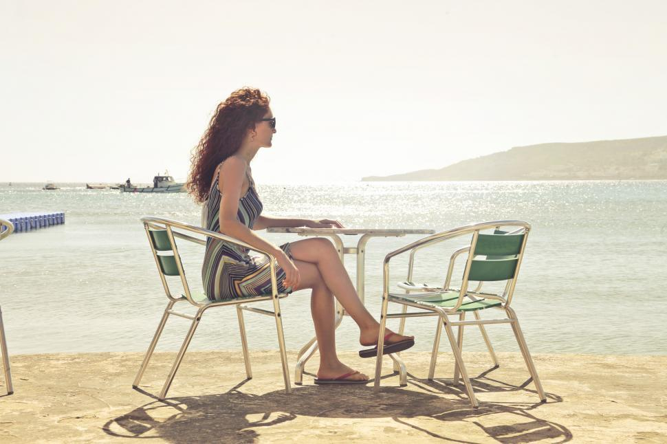 Download Free Stock HD Photo of Woman Sitting Cross-Legged on Armchair at Seashore Online
