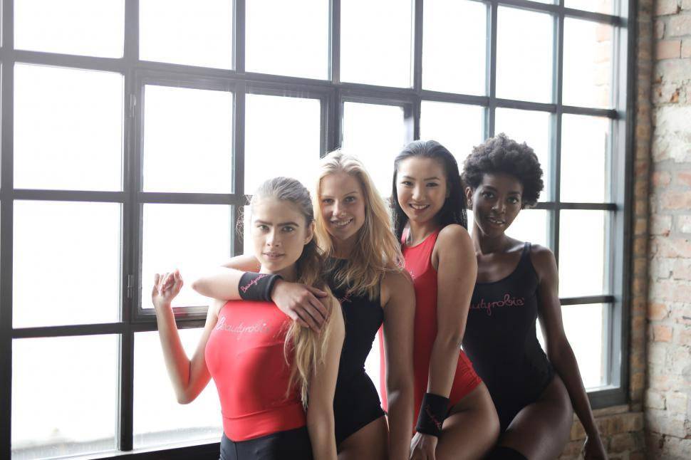 Download Free Stock HD Photo of Four Women Posing Near Glass Window In a Gym Online