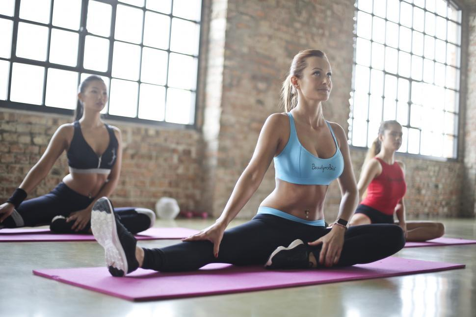 Download Free Stock HD Photo of Three Young Women Doing Exercises On Yoga Mats Online
