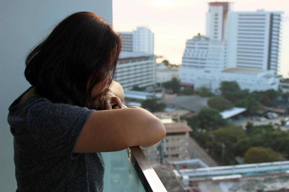 Download Free Stock Photo of A lady looks out at high-rise city buildings from a balcony