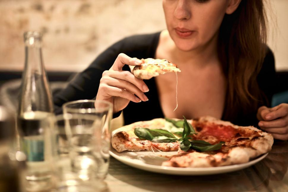 Download Free Stock HD Photo of Woman Holding Sliced Pizza To Eat Online