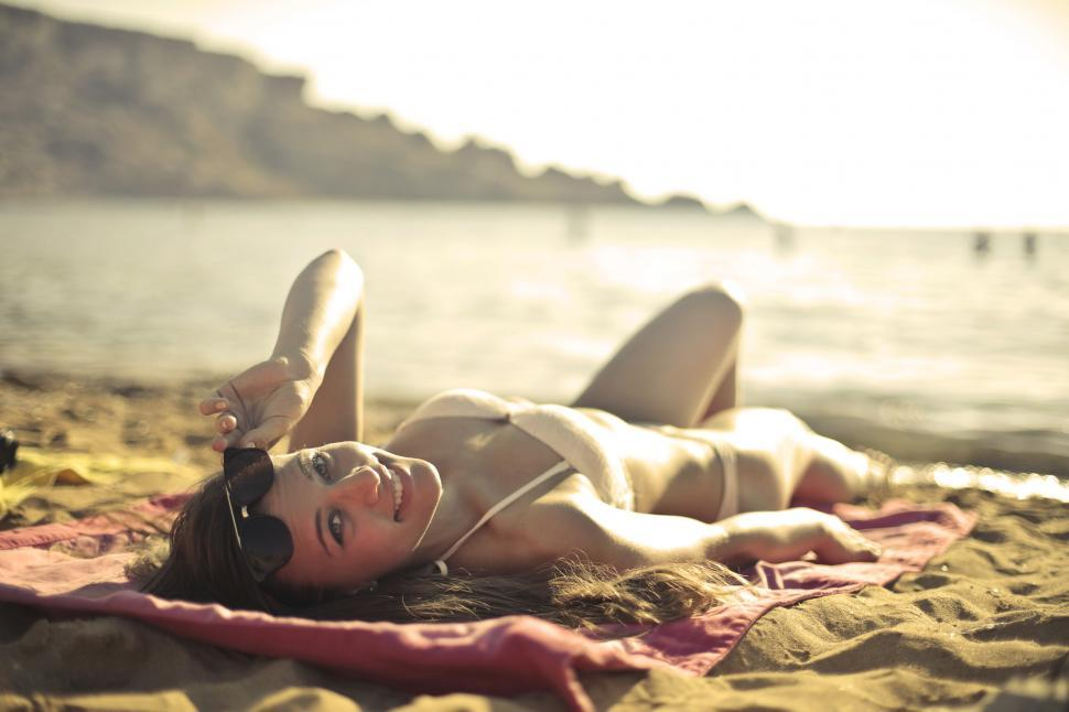 Download Free Stock HD Photo of Young Woman In White Bikini And Sunglasses Lying On Sand On The Online