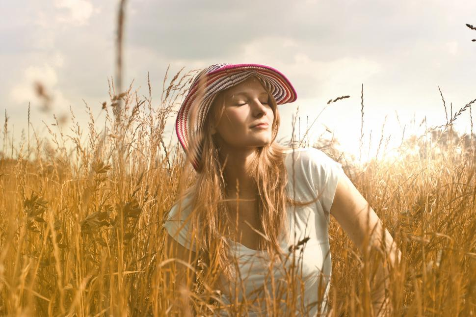 Download Free Stock HD Photo of Young woman in striped hat sitting with eyes closed in a wheat f Online