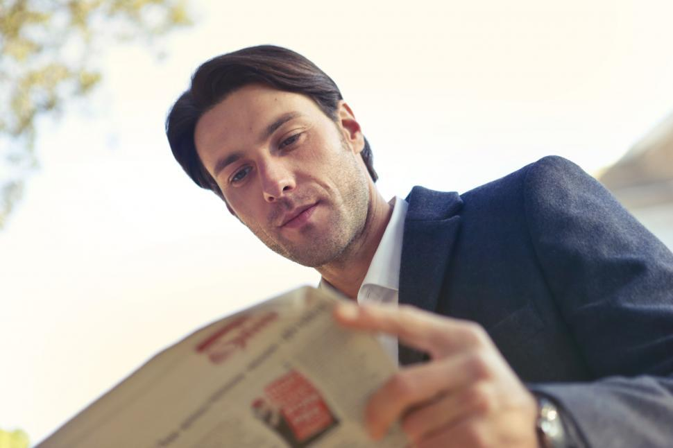 Download Free Stock Photo of Young Man In Blue Blazer Reading a Newspaper