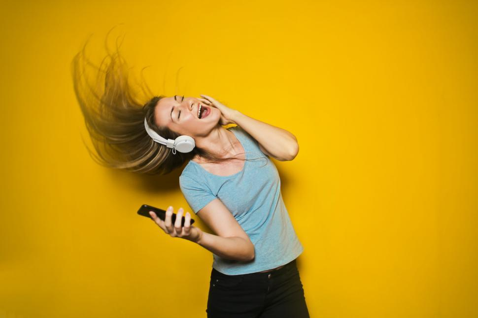 Download Free Stock HD Photo of Excited woman dancing and listening music with headphones and sm Online