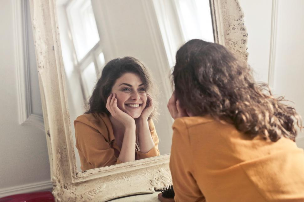 Download Free Stock Photo of Young woman looking herself reflection in mirror at home