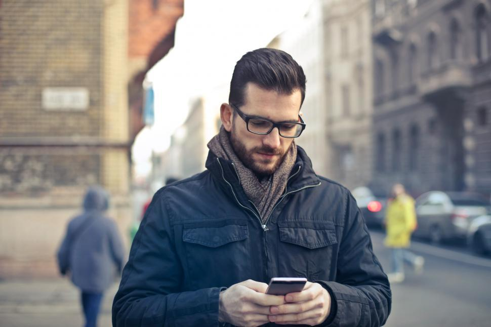 Download Free Stock HD Photo of Young Bearded Man Using His Smartphone To Text While Walking On Online