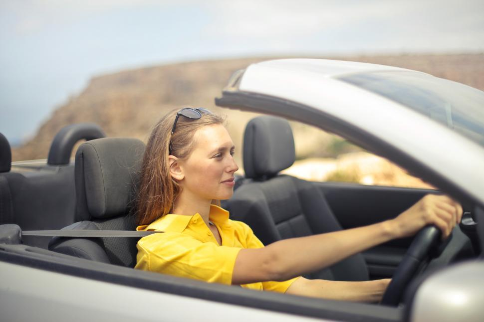 Download Free Stock HD Photo of Young Woman Wearing Half-Sleeved Yellow Shirt Driving Car Online