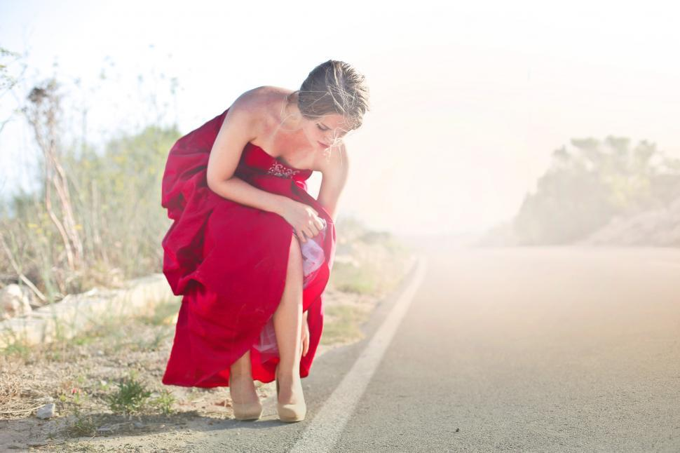 Download Free Stock HD Photo of Young Adult Woman In Red Party Gown Dress Adjusting Her Shoes Online