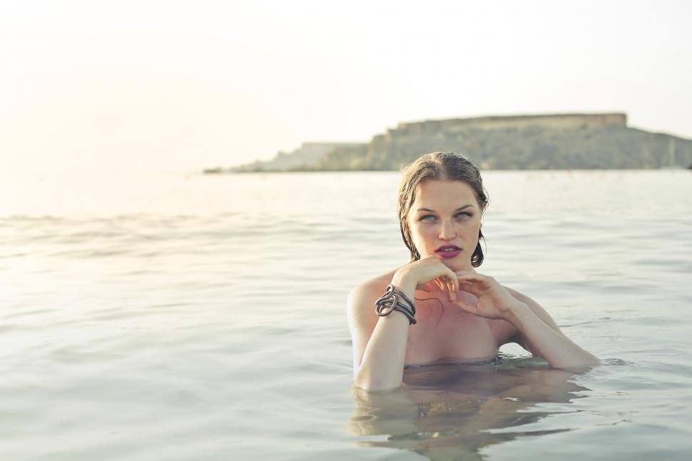 Download Free Stock HD Photo of Female Fashion Model Posing Semi Submerged In Sea Online