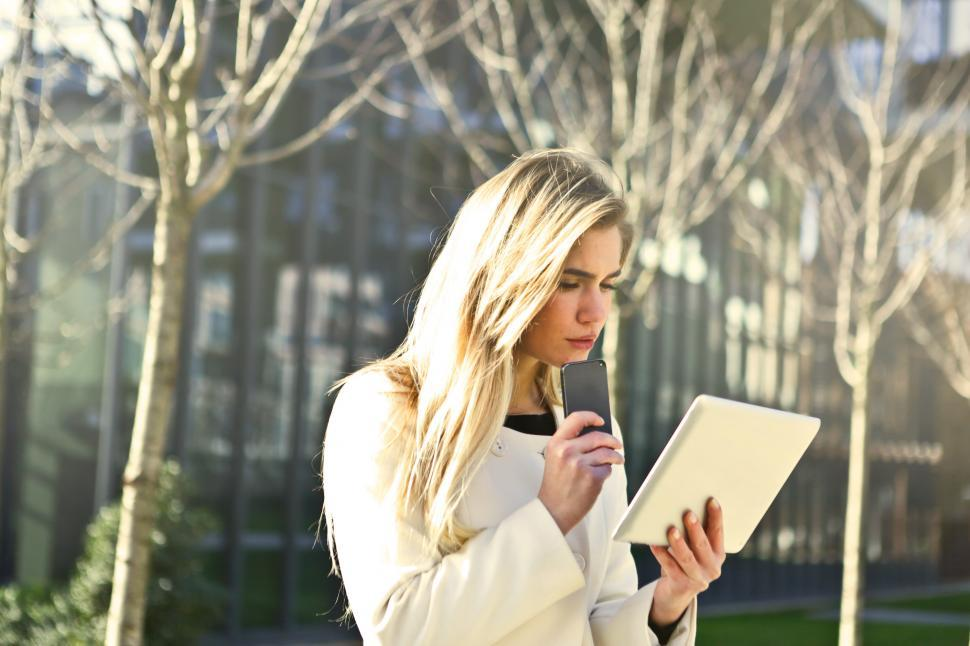 Download Free Stock HD Photo of Young Woman In White Jacket Using Smartphone And Tablet Online