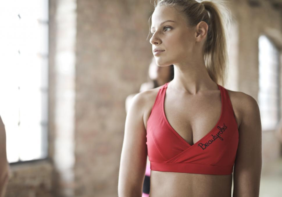 Download Free Stock HD Photo of A young blonde woman in sports bra looks at her right Online