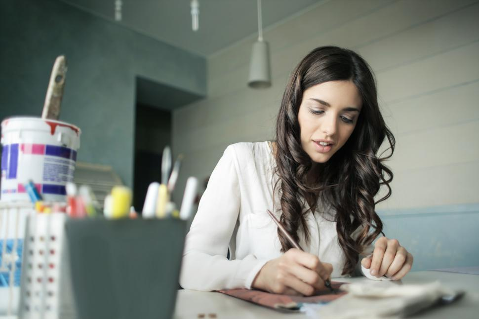Download Free Stock HD Photo of A beautiful young woman writing on the papers at her desk Online