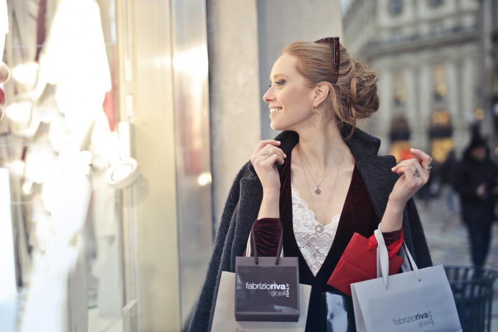 Download Free Stock HD Photo of A beautiful young blond woman holding shopping bags in her hands Online