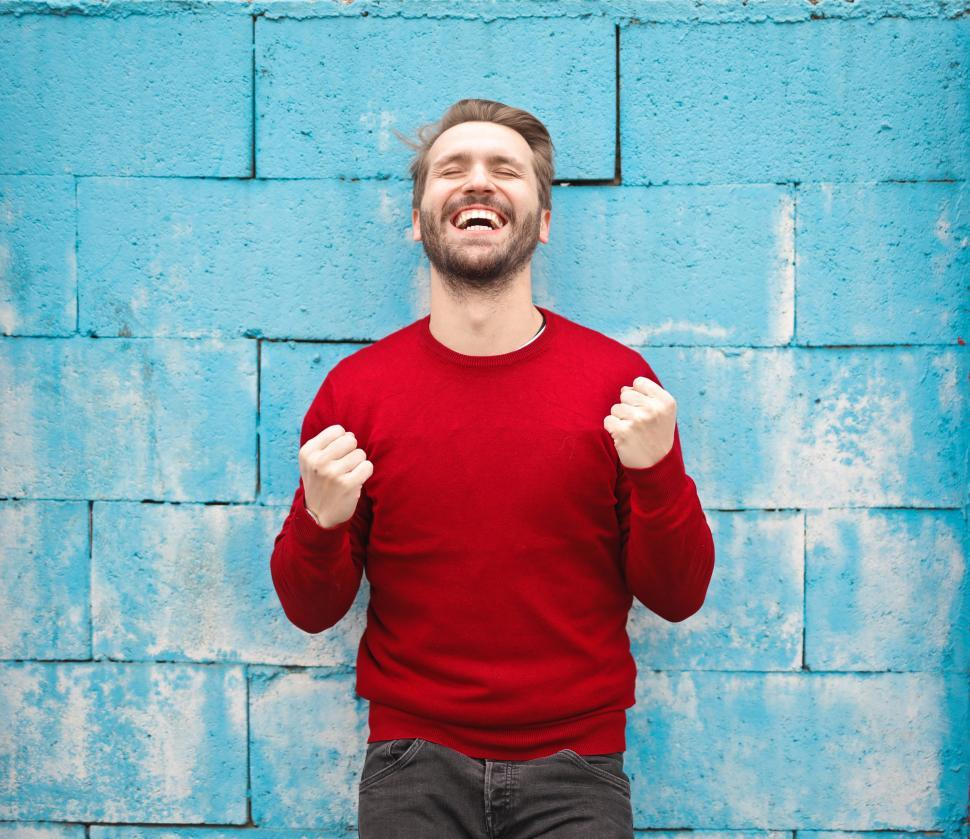 Download Free Stock Photo of A happy young caucasian man in red sweater standing against a br