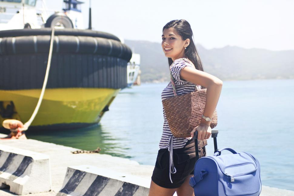 Download Free Stock HD Photo of A yound brunette walking with her travel bag Online