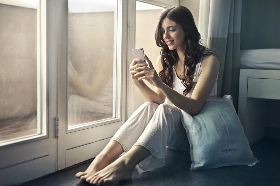 Download Free Stock Photo of A young woman sitting on the floor looking at her mobile phone