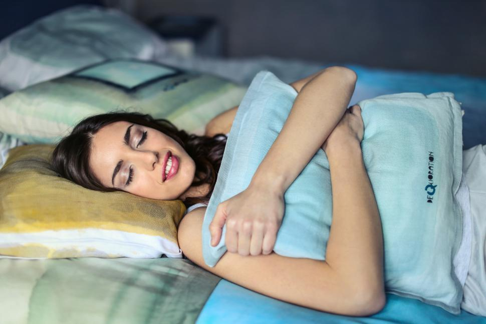 Download Free Stock HD Photo of A young brunette woman sleeping while embracing a pillow Online