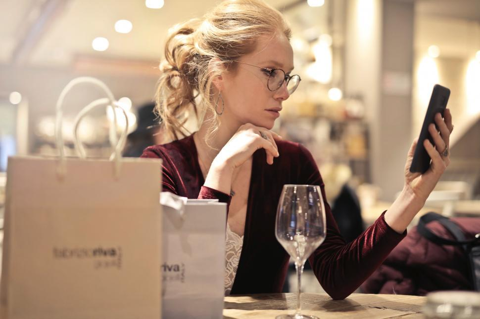 Download Free Stock HD Photo of A young blond woman looks at her mobile in a restaurant Online