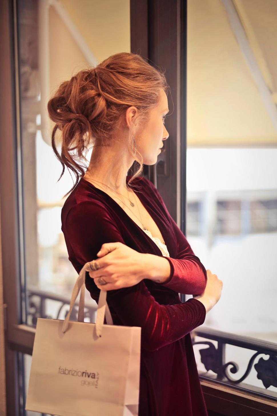 Download Free Stock Photo of A young blond woman with elegant hair bun holding a shopping bag