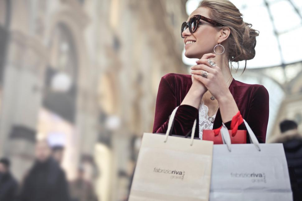 Download Free Stock Photo of A young blonde woman holding shopping bags in her hands