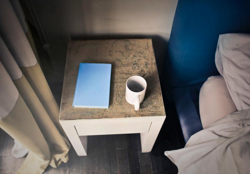 Download Free Stock HD Photo of A diary and a coffee mug on the bed side table Online
