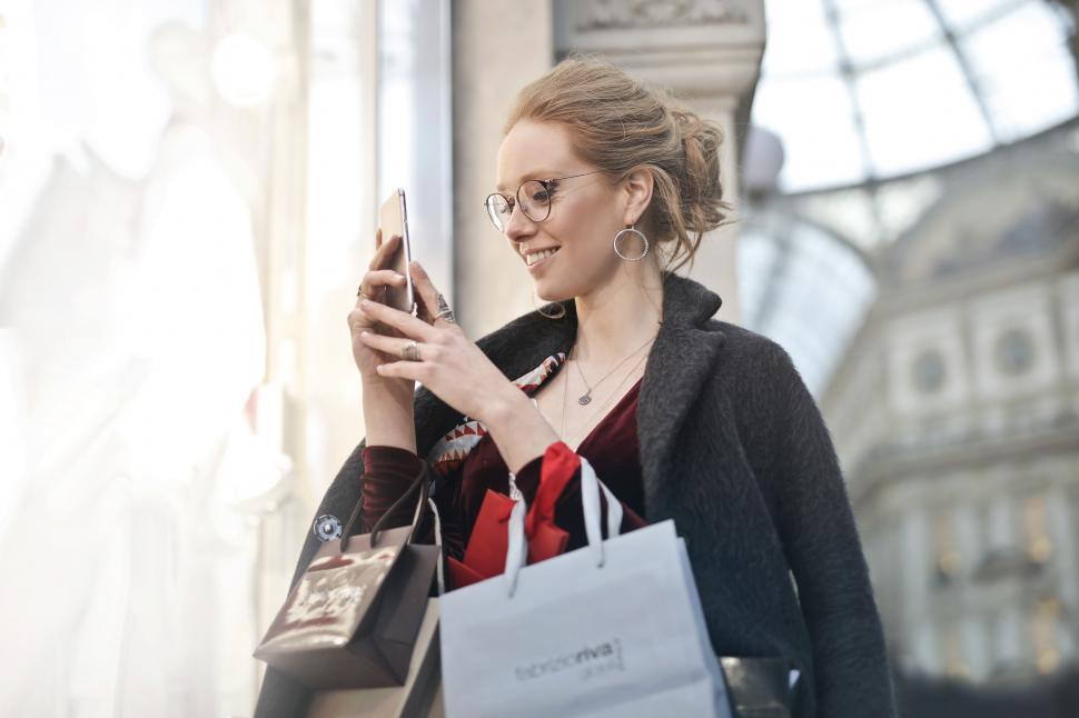 Download Free Stock Photo of A young blond woman looks at her mobile phone while holding shop
