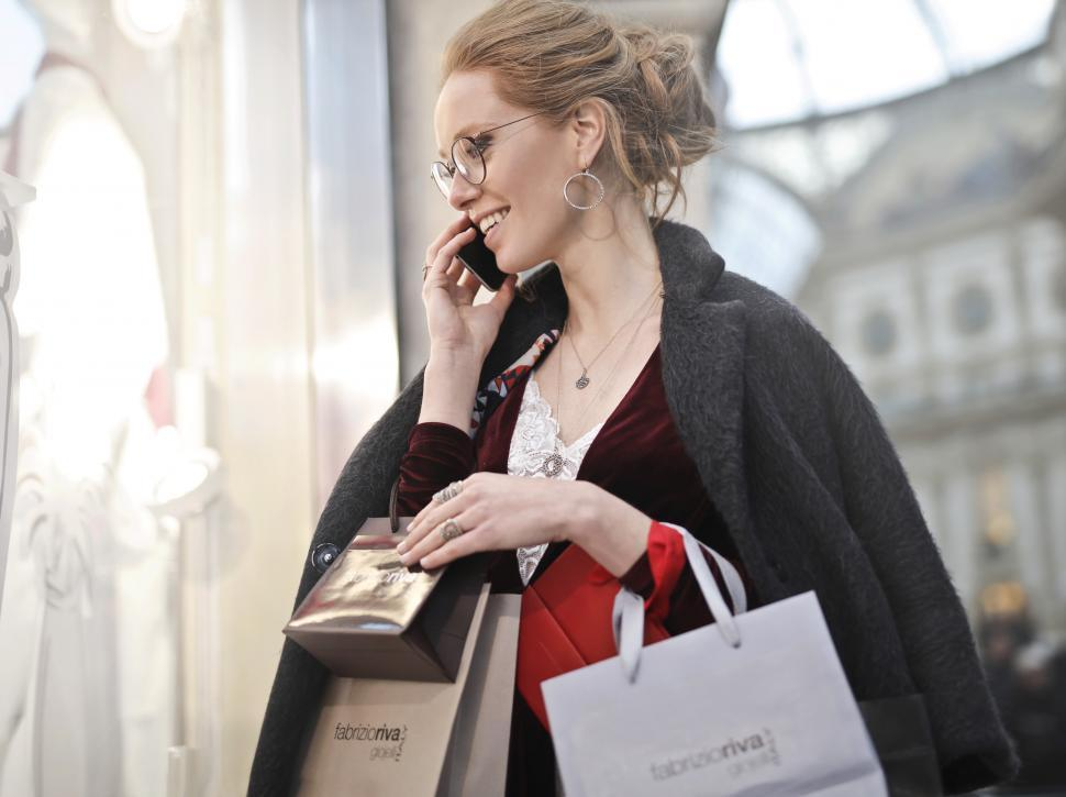 Download Free Stock HD Photo of A young blond woman calling on her mobile phone while holding sh Online