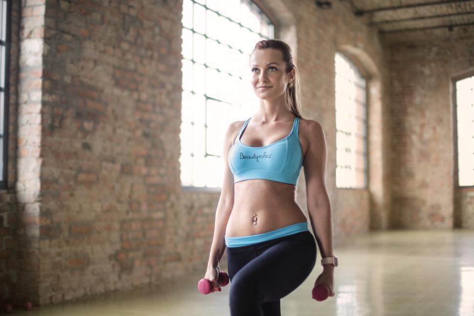 Download Free Stock HD Photo of A young blonde woman doing weight exercise in the gym with bumbb Online