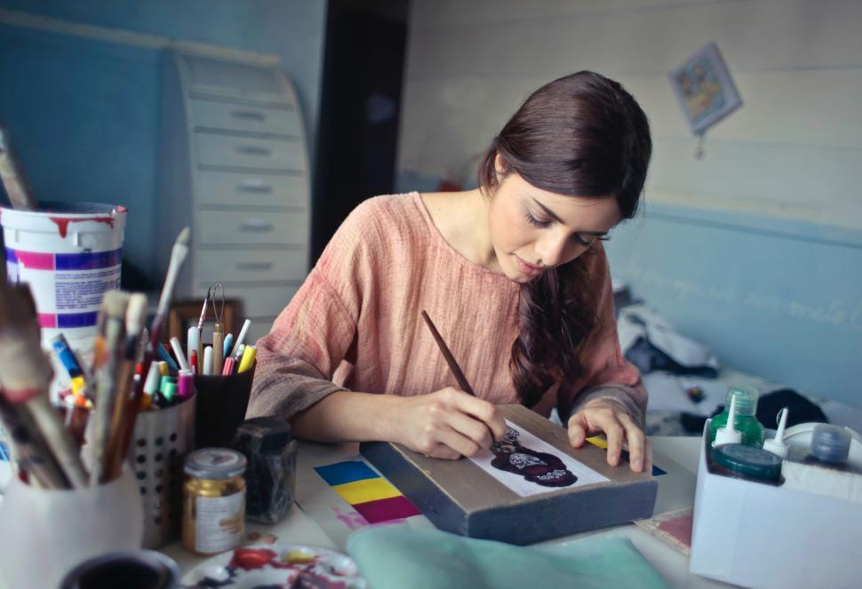 Download Free Stock HD Photo of A young woman painting with a brush in her hand Online