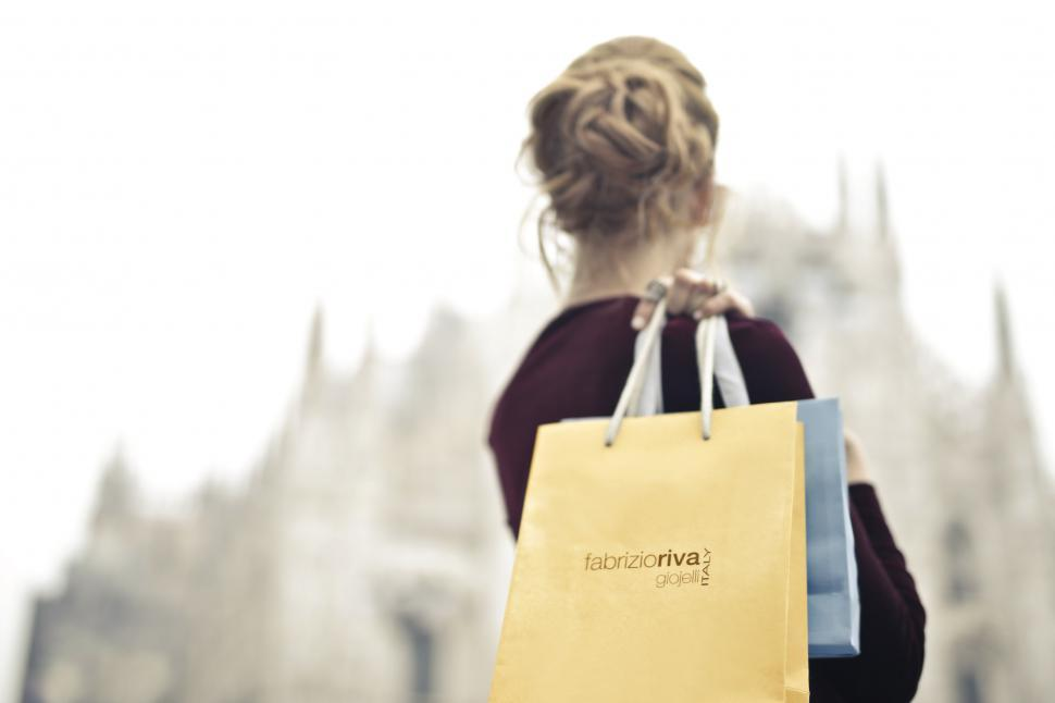Download Free Stock HD Photo of A young blonde woman holding shopping bags in her hand on her sh Online