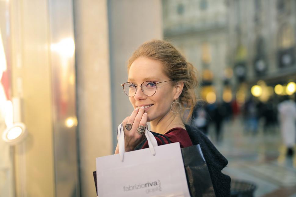 Download Free Stock Photo of A young blonde woman holding shopping bags in her hand looks ove