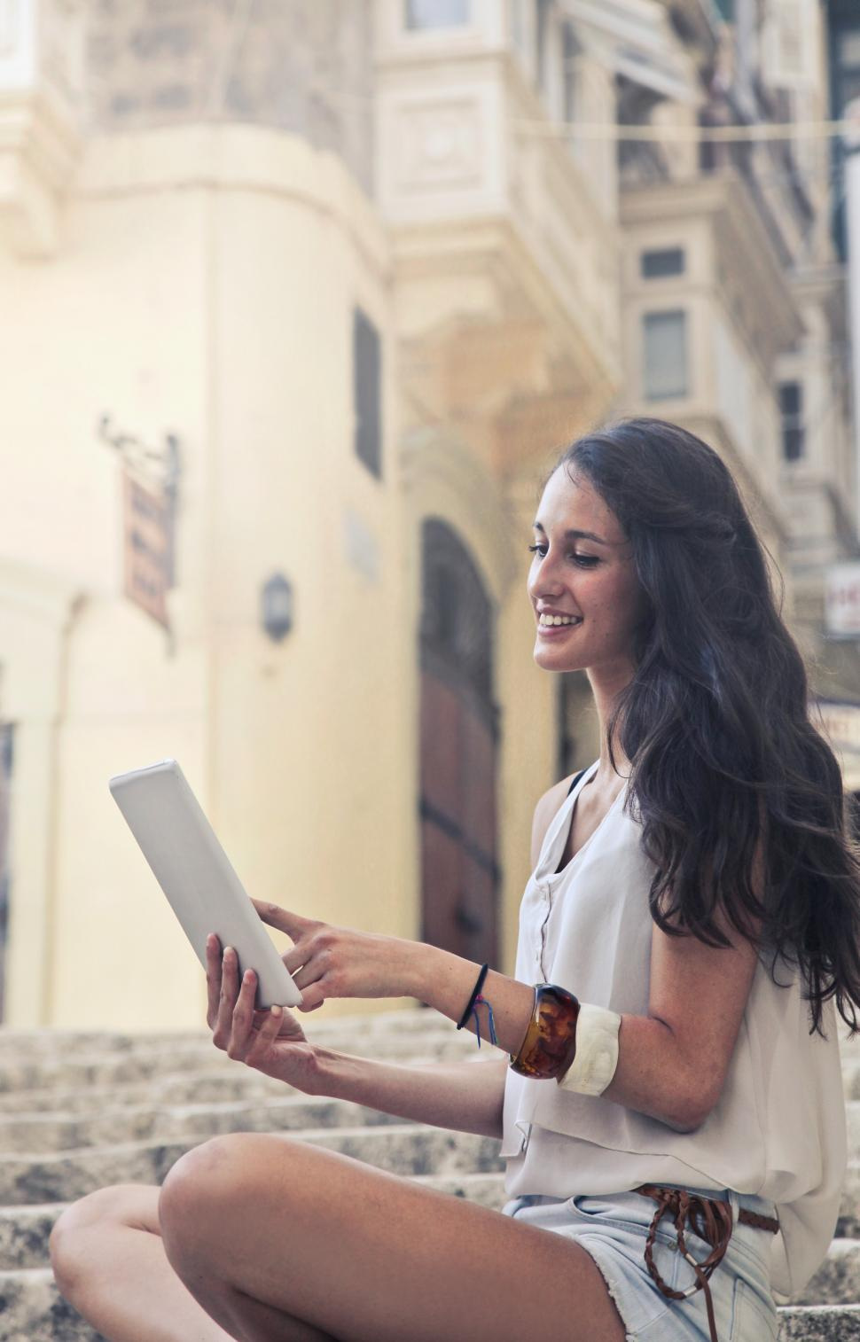 Download Free Stock HD Photo of A young brunette woman looking at her tablet screen Online
