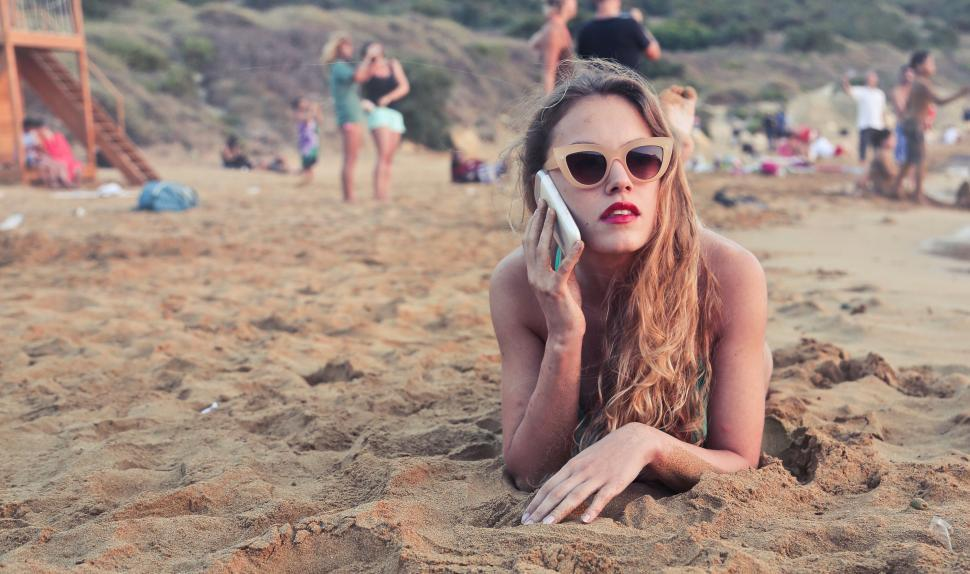 Download Free Stock HD Photo of A young blonde woman calling on her mobile phone in the sand Online