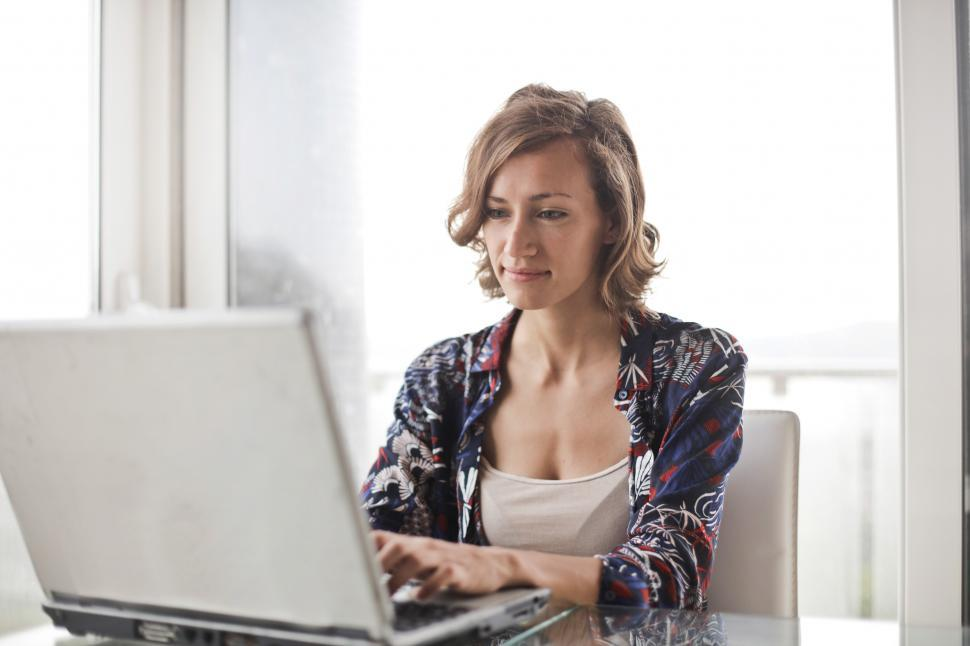 Download Free Stock HD Photo of A young blonde woman working on her laptop Online
