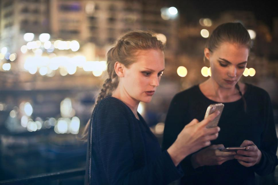 Download Free Stock Photo of Two young blonde women texting on their mobile phones