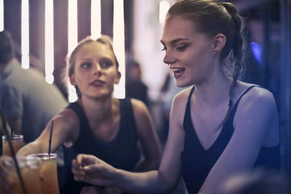 Download Free Stock HD Photo of Two young blonde women sitting in a bar Online
