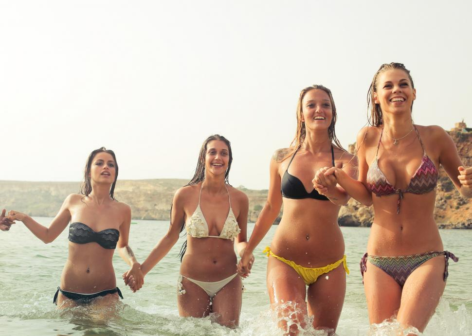 Download Free Stock HD Photo of A group of blondes and brunettes wearing bikinis posing in knee Online