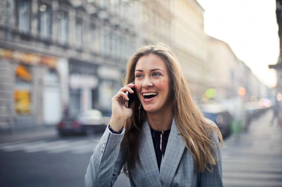Download Free Stock Photo of A young blonde woman calling on her mobile phone in the street