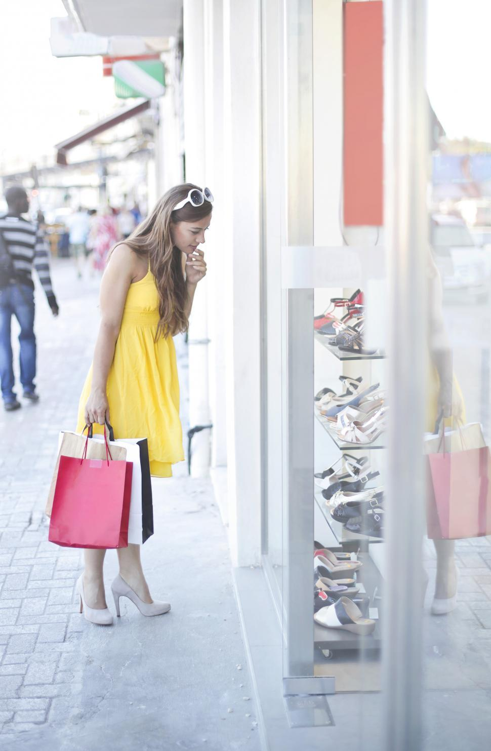 Download Free Stock HD Photo of A young blonde woman with shopping bags looks at a shoes display Online