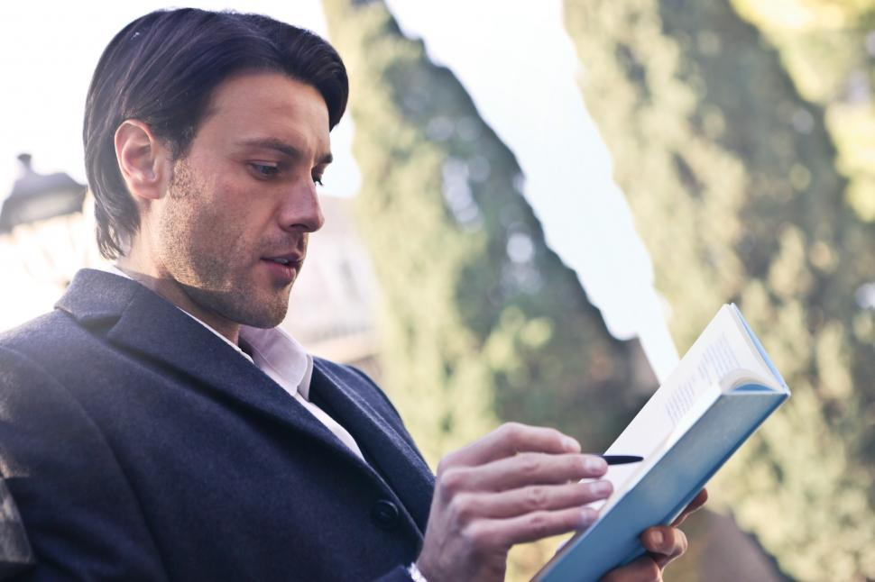 Download Free Stock HD Photo of A young caucasian man writing on a notebook in the park Online