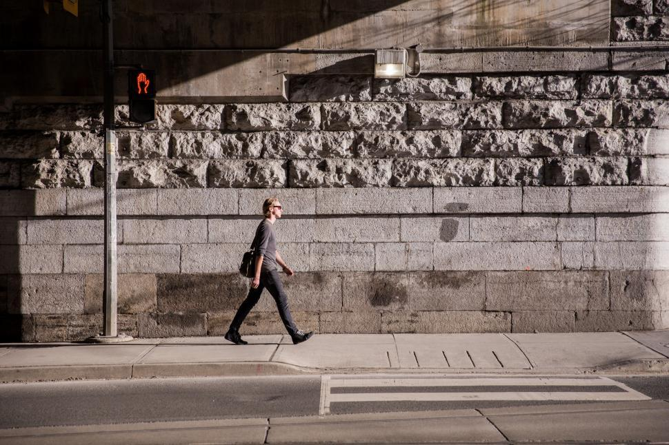 Download Free Stock HD Photo of A young caucasian man walking in urban sunlight Online