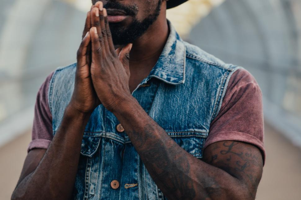 Download Free Stock Photo of A young African American man with folded hands