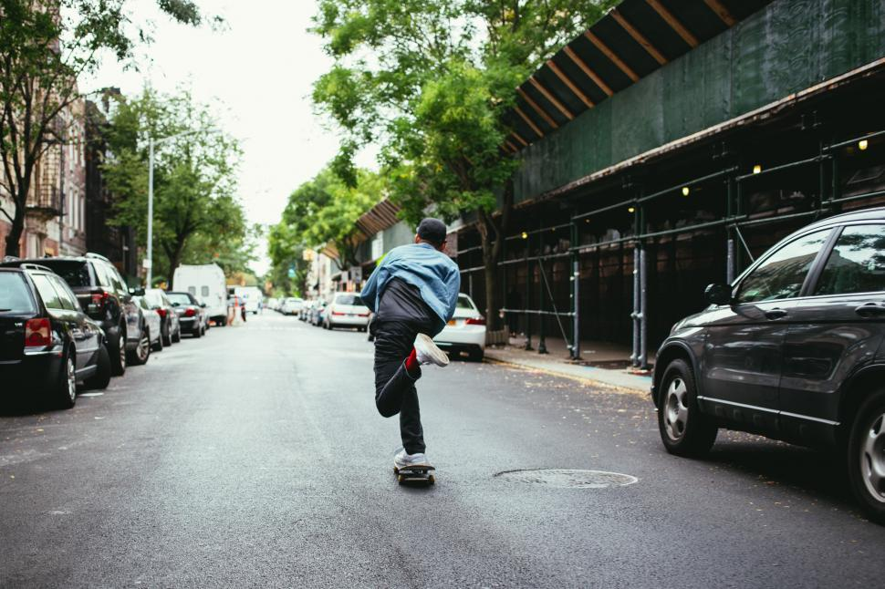 Download Free Stock HD Photo of A young caucasian skateboarder in the street Online
