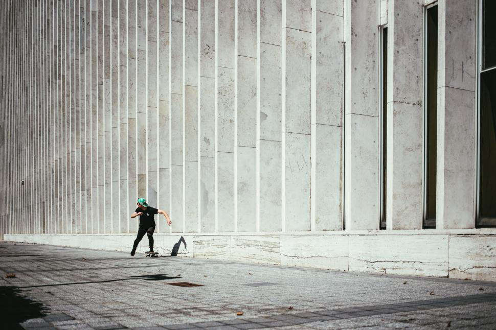 Download Free Stock HD Photo of A young caucasian skateboarder rides past a city building Online